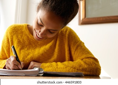 Portrait of a young african american woman writing in book