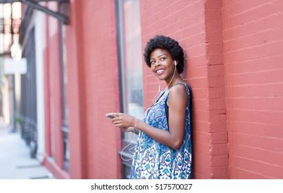 Portrait of young African American woman listening to music. Photographed in Soho, NYC.