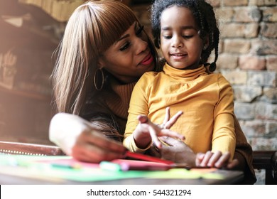 Portrait of a young African American woman and her daughter learning together.