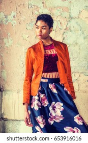 Portrait of Young African American Woman in New York, wearing fashionable orange red jacket, dark red under top, dark blue flower patterned skirt, standing by painted wall on street, looking away.