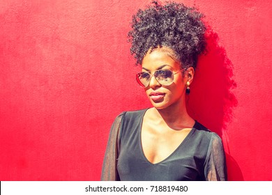 Portrait of Young African American Woman in New York. Young black woman with afro hairstyle wearing long sleeve mesh sheer shirt, sunglasses, standing against red background under sun.
