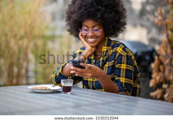 Portrait of young african American woman smiling outside looking at mobile phone