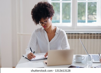 Portrait of a young African businesswoman taking notes at the modern office space.