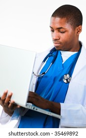 Portrait of an young African doctor working on a laptop isolated against white