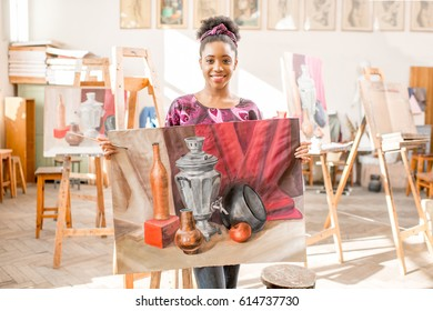 Portrait of a young african ethnicity student standing with paintings at the university studio