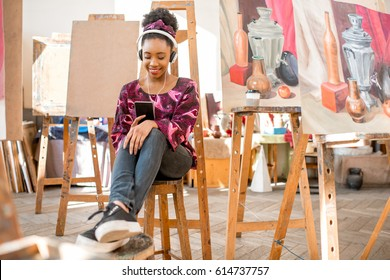 Portrait of a young african ethnicity student sitting with phone during the break at the studio for painting