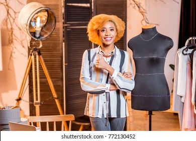 Portrait of a young african fashion designer standing near the mannequin at the studio
