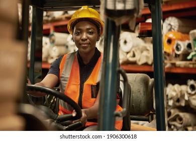 Portrait eines jungen afrikanischen Gabelstaplerbetreibers, der Kisten um ein Textillager bewegt