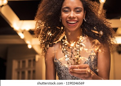 Portrait of young african girl holding sparkle stick under the patio outdoor. Happy smiling woman celebrating with fireworks. Elegant woman holding a bengal light for new year's eve party.