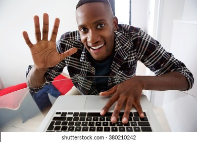 Portrait of young african guy waving while video chatting on laptop at home