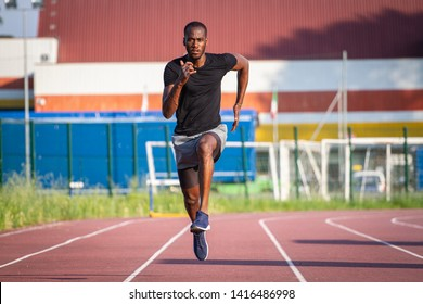 Portrait  of young african male athlete is running on race track in athletics stadium.