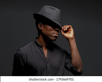 portrait of a young African man in a black hat. Black background studio photography