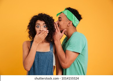 Portrait of a young african man dressed in summer clothes whispering a secret to his girlfriend isolated over yellow background