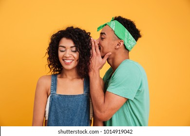 Portrait of a young african man dressed in summer clothes whispering a secret to his smiling girlfriend isolated over yellow background