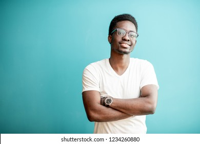 Portrait of a young african man dressed in white t-shirt standing on the colorful background