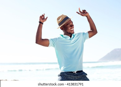Portrait of young african man having fun at the beach on summer day