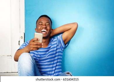 Portrait of young african man laughing and looking at cellphone