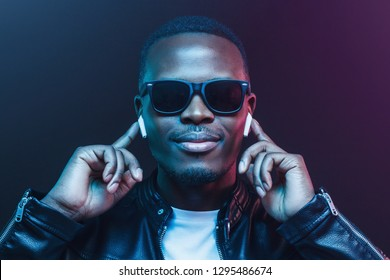 Portrait of young african man listening music with wireless earphones