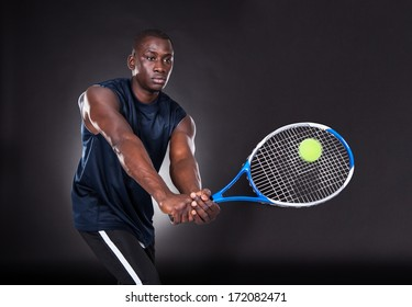 Portrait Of Young African Man Playing Tennis On Black Background