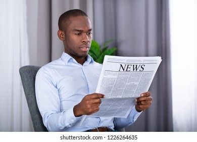 Portrait Of A Young African Man Reading Newspaper