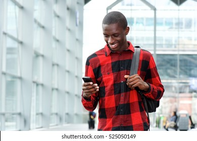 Portrait of young african man reading a text message on his mobile phone at train station