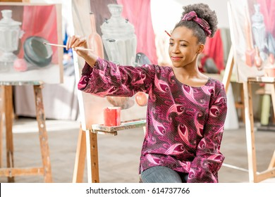 Portrait of a young african student sitting at the studio for painting