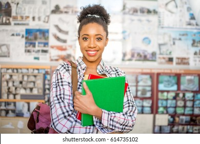 Portrait of a young african student standing with books in front of the degree project at the university