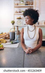 Portrait of young african woman at juice bar, she is standing behind counter looking away and thinking.