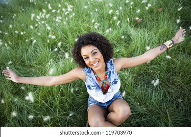 Portrait of a young african woman with raised arms in the park