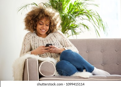 Portrait of young african woman relaxing at home and using mobile phone