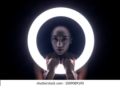 Portrait young african woman with ring flash effect. Round LED Circle Lamp in dark studio