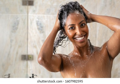 Portrait of young african woman in shower washing hair with shampoo and conditioner at spa. Happy black woman massaging hair with shampoo in shower and looking at camera. Girl washing with copy space.