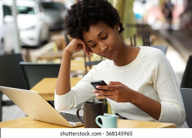 Portrait of a young african woman sitting at outdoor cafe using cellphone