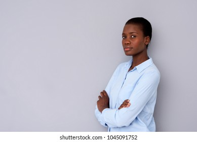 Portrait of young african woman standing with arms crossed and staring at camera