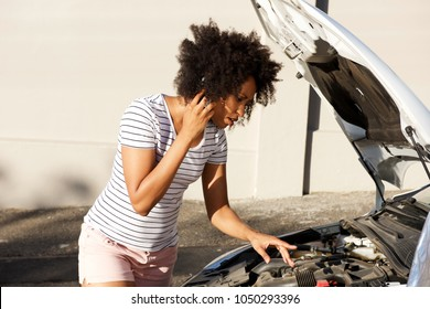 Portrait of young african woman standing by broken down car parked on the road and calling for assistance