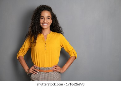 Portrait of young african woman standing with hands on waist and looking at camera. Confident stylish girl standing against grey background. Happy young mixed race woman smiling i with copy space.