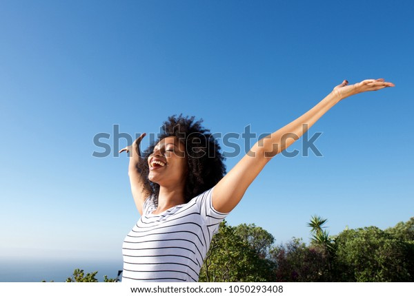 Portrait of young african woman standing outdoors with arms raised and laughing