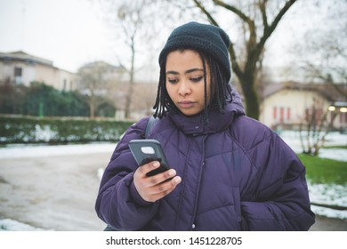 portrait of young african woman using smartphone in the street – technology, communication, break time