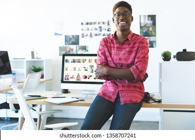 Portrait of young African-American graphic designer looking and smiling at camera while sitting at desk in office