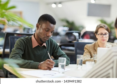 Portrait of young African-American man taking notes during training class in office, copy space