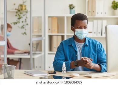 Porträt eines jungen afroamerikanischen Mannes, der Gesichtsmaske trägt und Hände in den Händen beim Arbeiten im Büro nach der Pandemie, Kopienraum