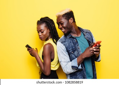 Portrait of a young afro american couple standing back to back using mobile phones isolated over yellow