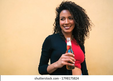 Portrait of young Afro american latin woman enjoying and drinking a bottle of beer, against yellow background. Lifestyle concept.
