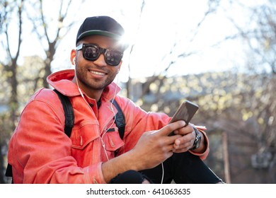 Portrait of a young afro american man in cap and sunglasses sitting and listening to music with earphones outdoors