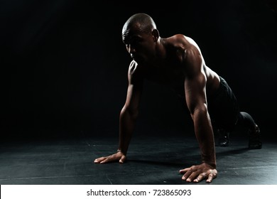 Portrait of young afro american sports man doing pushup exercise, looking away, on black background