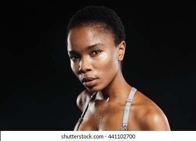 Portrait of a young afro american woman in sports wear isolated on the black background