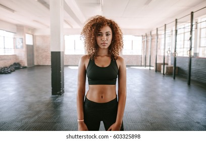 Portrait of young afro american woman in sportswear. Fitness model  standing in the gym and looking at camera.