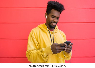 Portrait of young afro man using his mobile phone with earphones against red wall. Technology and lifestyle concept.