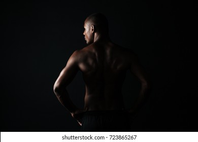 Portrait of young afroamerican sports man, standing back, looking aside, isolated on black background
