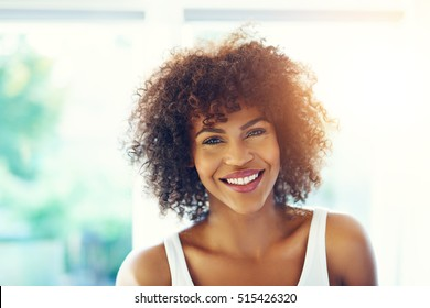 Portrait of young afro-american woman with curly hair looking at camera and smiling on blurred inside background.